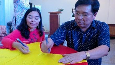 """Tác giả Quế Mai và nhạc sĩ Đinh Trung Cẩn cùng ký tên lên lá cờ Tổ quốc trong buổi ra mắt tập thơ """"Tổ quốc gọi tên mình"""""""