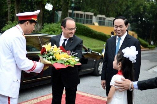 Một bé gái tặng hoa ông Hollande trong lễ đón. Ông Hollande là tổng thống Pháp đầu tiên thăm Việt Nam sau 12 năm, kể từ chuyến thăm của Tổng thống Jacques Chirac vào năm 2004. (Ảnh: AFP)