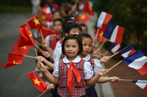Các học sinh vẫy cờ Việt Nam và Pháp trước lễ đón Tổng thống Hollande tại Phủ Chủ tịch. (Ảnh: AFP)