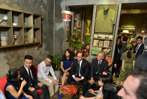 Tổng thống Hollande còn ghé một quán cà phê ở phố cổ và trò chuyện thân mật với các cựu du học sinh Việt Nam tại Pháp. (Ảnh: AFP)