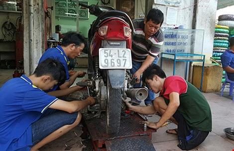 Anh Phúc (áo thun sọc ngang) cùng các thợ sửa xe của tiệm. Ảnh: HỒNG MINH