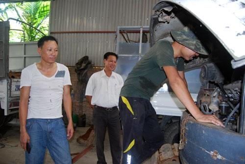 """Anh Vũ Phương Hùng (phải) đang được """"tiền bối"""" Vũ Văn Đoàn (ngoài cùng bên trái) hướng dẫn sửa một chiếc xe cũ tại xưởng. Ảnh: M.L"""
