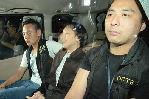 Quách Vĩnh Hồng (ngồi giữa), một trùm hội Tam Hoàng bị bắt ngày 21.7 khi vừa xuống sân bay Hong Kong