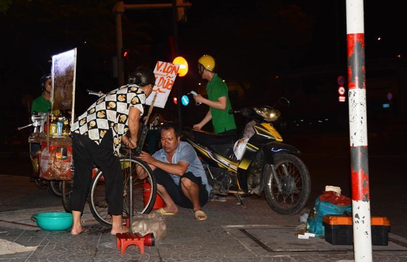 Hình ảnh người phụ nữ cặm cụi vá xe vào ban đêm ở ngã tư đường Hàm Nghi – Nam Kỳ Khởi Nghĩa, quận 1, TP.HCM đã trở nên quen thuộc với nhiều người
