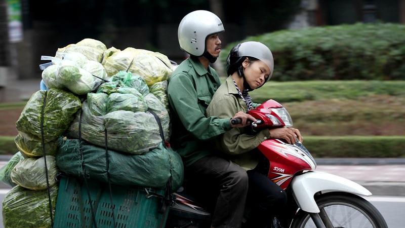 Ngồi ngủ đã khó, người phụ nữ này vẫn ngủ ngon lành trong khi người đàn ông điều khiển xe máy trên đường Trần Duy Hưng.