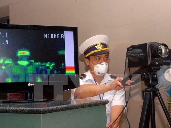 Kiểm tra thân nhiệt hành khách ở cửa khẩu Nội Bài. (Ảnh: Hữu Việt/TTXVN)