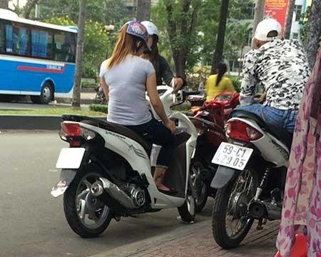 Hai cô gái bán dâm dừng xe cạnh một thanh niên làm nhiệm vụ canh chừng. Ảnh: HT.