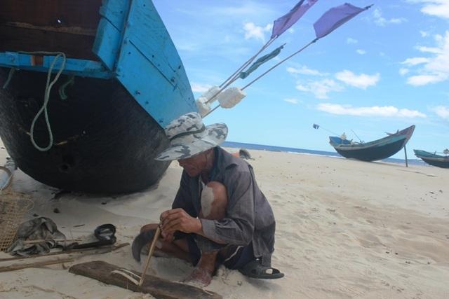 Ông Phụng ngồi trên cát gia cố lại con thuyền sau mấy tháng không đi biển