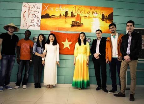 Hai nữ sinh Việt Nam trong trang phục áo dài chụp ảnh cùng các bạn học tại Đại học ADA.
