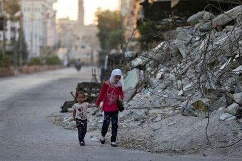 Hai trẻ em đi bộ qua một tòa nhà đổ nát trong ngày lễ Eid al-Fitr tại khu phố Douma, Damascus, Syria. (ảnh: Reuters).