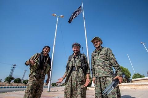 Những tay súng thuộc Các đơn vị Bảo vệ Nhân dân người Kurd đứng cạnh cờ Nhà nước Hồi giáo ở thị trấn Tel Abyad, Syria.