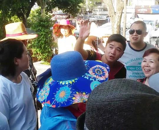 Một người Trung Quốc (giơ tay) từ xe của Công ty Silent Bay bước xuống, giới thiệu cho khách Trung Quốc tham quan tại Tháp Bà (TP Nha Trang) Ảnh: KỲ NAM
