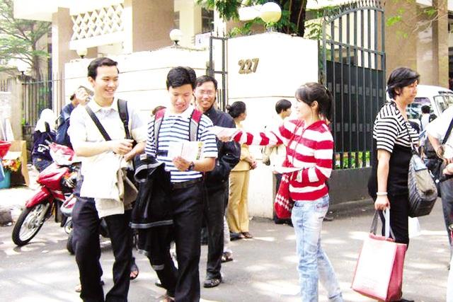 Nguyễn Thúy Hà - sinh viên ĐH Kinh tế Quốc dân (từ phải qua) chọn việc phát tờ rơi để có thu nhập mua vé tàu xe và tiêu dịp Tết. Ảnh: Q.A