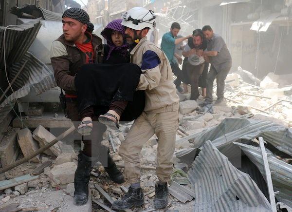 Lực lượng phòng vệ dân sự Syria sơ tán người bị thương khỏi hiện trường một vụ không kích tại Hayy Aqyul, thành phố Aleppo ngày 22/4. (Nguồn: AFP/TTXVN)