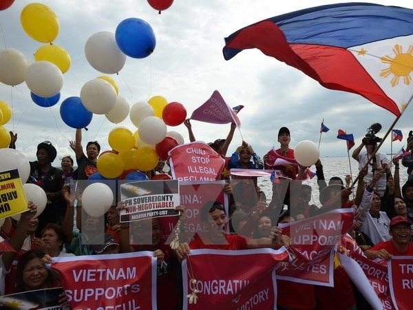 Các nhà hoạt động Philippines vui mừng sau phán quyết của Tòa Trọng tài ở Lahay trong cuộc tuần hành tại Manila ngày 12/7 vừa qua. (Ảnh: AFP/TTXVN)