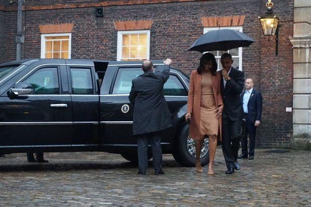 Tổng thống Obama che ô cho vợ khi bước xuống từ ô tô tại cổng cung điện Kensington.
