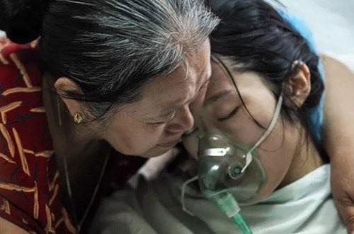 Đậu Thị Huyền Trâm trong vòng tay mẹ trong những ngày được điều trị tại Bệnh viện K, ảnh chụp sáng 26-7 trước khi chị Trâm về quê nhà Hà Tĩnh trong chiều cùng ngày. Sau thời gian dài chống chọi với bệnh tật, chị trút hơi thở cuối cùng chiều 27-7 (Ảnh: Tuổi Trẻ)