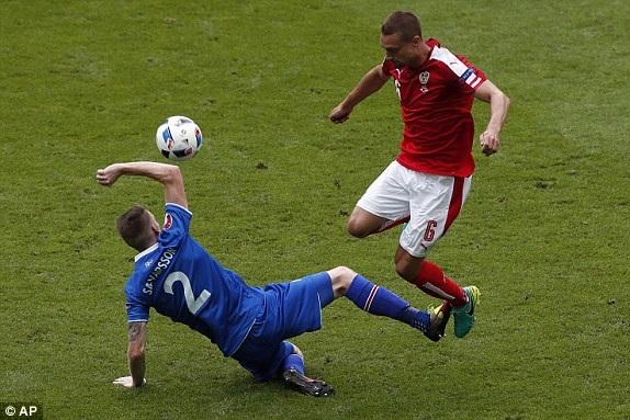 Stefan Ilsanker (phải) nhảy lên tránh pha vào bóng của Birkir Saevarsson
