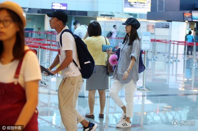 Lâm Tâm Như diện quần jeans trắng, áo sơ mi rộng thùng thình để giấu bụng bầu, kết hợp với giày thể thao.