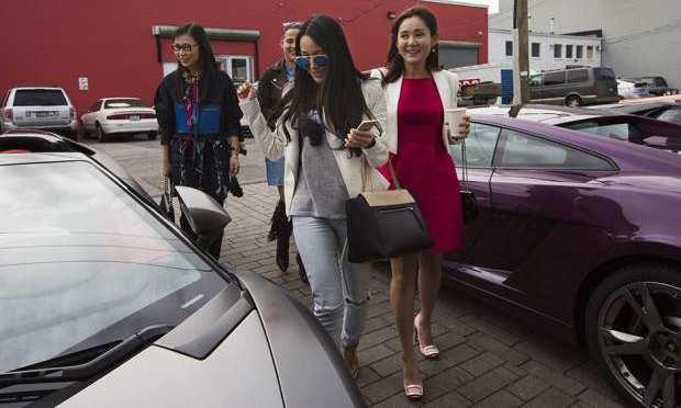 Những cô gái con nhà giàu Trung Quốc đang xem gian hàng siêu xe Lamborghini ở Vancouver.
