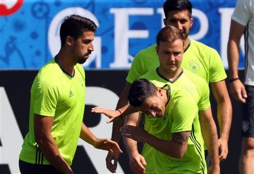 Ozil cúi đầu dường như né cú đòn của Khedira khi họ trêu đùa nhau trên sân tập