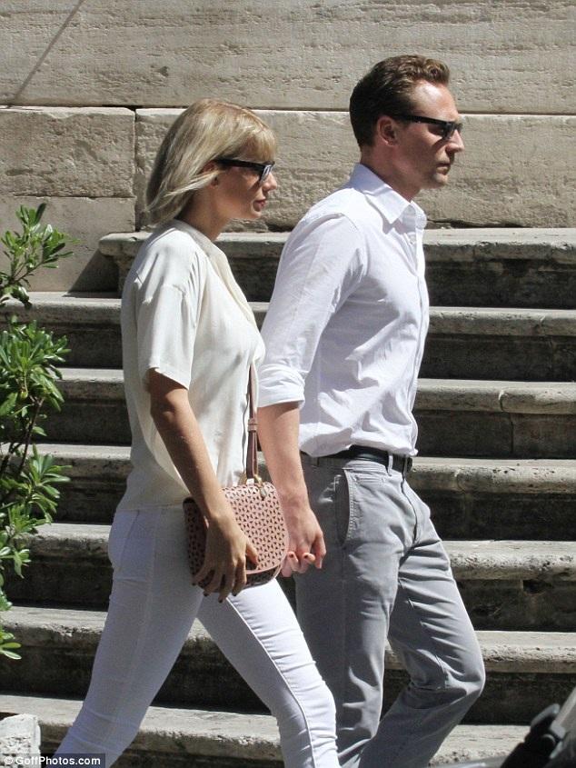 Nam diễn viên người Anh diện áo sơ mi trắng trong khi bạn gái anh thanh lịch với quần jeans trắng ôm sát màu trắng và áo sơ mi cùng màu. Taylor kết hợp trang phục của cô với túi đeo chéo nhẹ nhàng và đôi sandal màu ghi sáng khiến tổng thể bộ trang phục thật đẹp mắt.