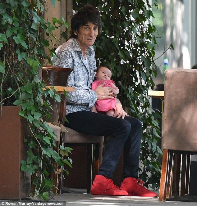Ronnie bế con gái trên tay trong khi vợ đang mải mê trò chuyện với một người bạn khác giới. Ngôi sao 69 tuổi có tổng cộng 6 người con.