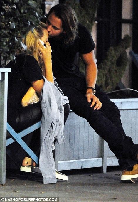 Margot Robbie tranh thủ trò chuyện trên điện thoại khi bạn trai tặng lên trán cô một nụ hôn tình cảm.