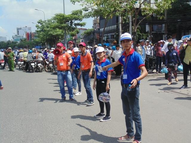 Dưới cái nắng gắt, các tình nguyện viên vẫn nắm tay nhau thành những dải phân cách nhằm đảm bảo giao thông đi lại. (Ảnh: Xuân Duy)