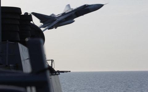Chiến đấu cơ Nga bay ngay phía trước tàu chiến Mỹ. Ảnh Reuters