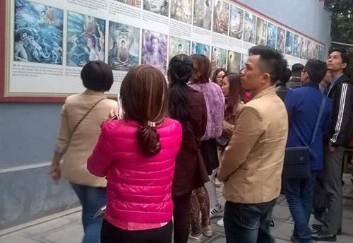 Các bạn trẻ tham quan các bức tranh giới thiệu về đức Phật.