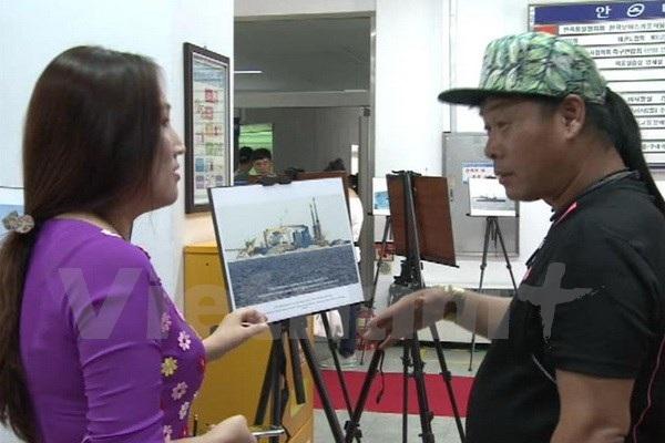 Một tình nguyện viên đang giới thiệu cho khách Hàn Quốc thăm quan triển lãm. (Ảnh: Phạm Duy/Vietnam+)