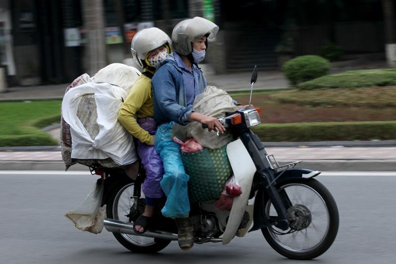 Để chở được nhiều hàng trên chiếc xe máy nhỏ bé, người buộc phải ngồi ép sát nhau.