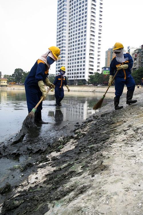 Công nhân vệ sinh những khu vực gần miệng cống xả thải sau khi mực nước hồ đã hạ xuống.