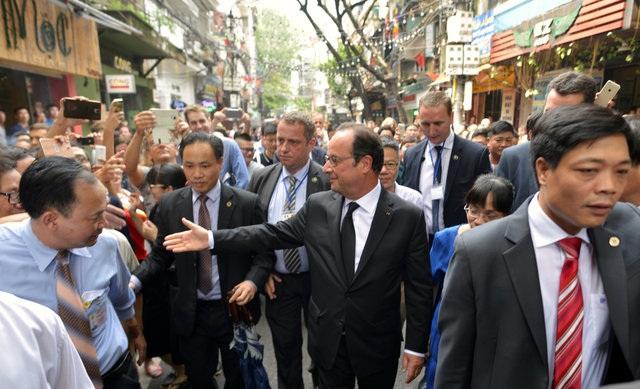 Ông Hollande bắt tay mọi người trong khi đi dạo phố phường của Hà Nội. (Ảnh: Reuters)