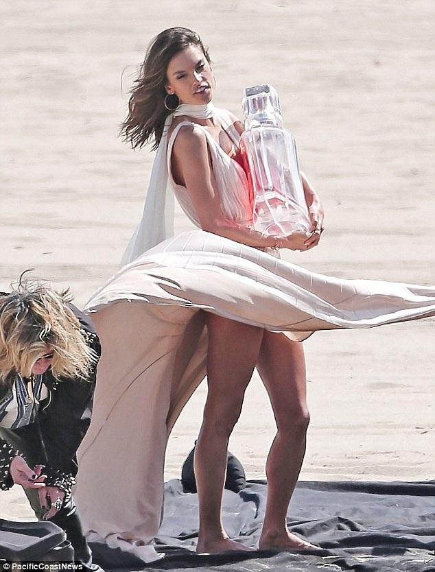 Alessandra chụp hình bên 1 chai nước hoa size khủng để quảng cáo cho sản phẩm nước hoa mới nhất mà cô đồng thiết kế