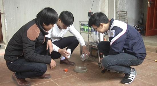 Học sinh Ngô Đức Thắng và Phạm Thành Trung với sự hướng dẫn của thầy giáo đang tổ chức thực nghiệm