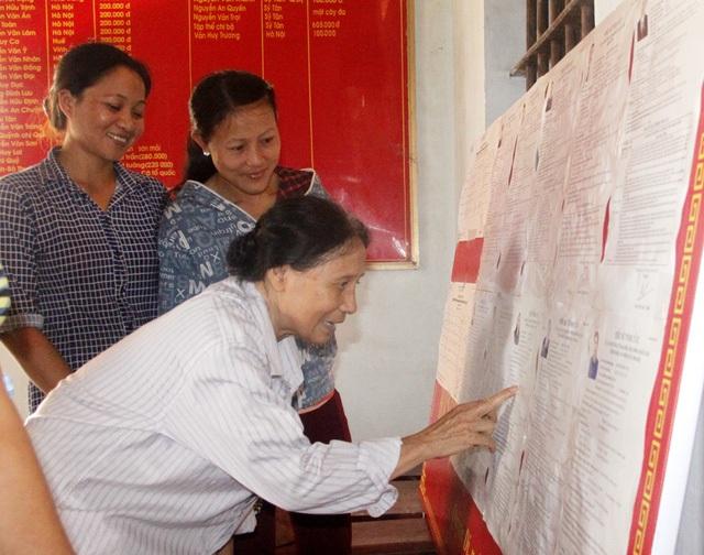 Cử tri nghiên cứu danh sách các ứng cử viên tại điểm bầu cử ở thị xã Hoàng Mai, Nghệ An. (Ảnh: Hoàng Lam)