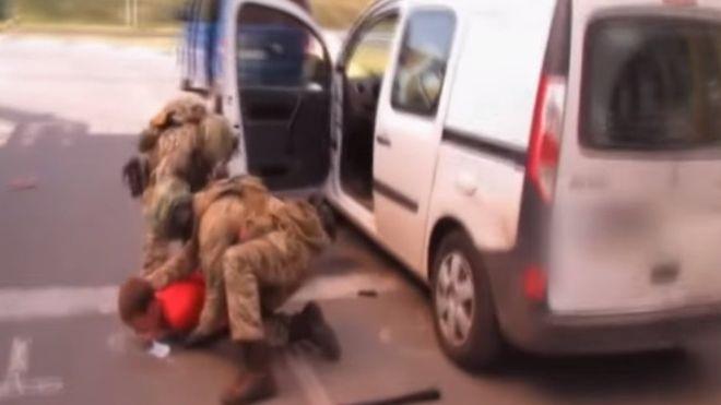 Nghi phạm (áo đỏ) bị bắt giữ tại biên giới giữa Ukraine và Ba Lan hồi tháng 5 (Ảnh: SBU)