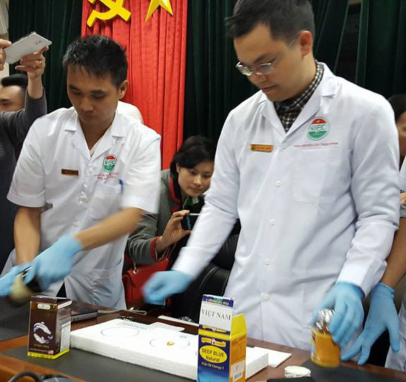 Cán bộ Viện Kiểm nghiện An toàn thực phẩm quốc gia tiến hành thực nghiệm đổ dầu ra tấm xốp. Ảnh: H.Hải