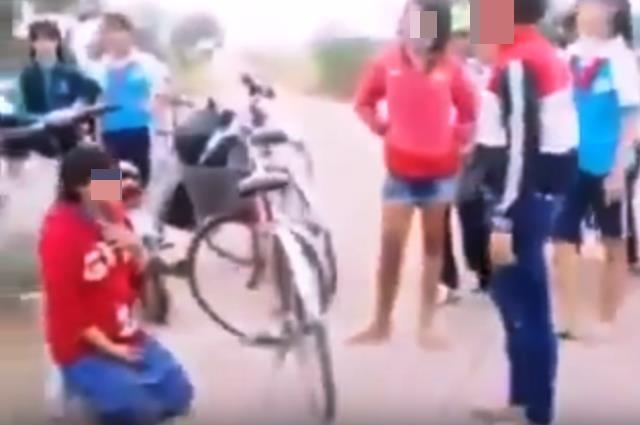 Cô gái uy hiếp cô nữ sinh– sự việc diễn ra ngay giữa đường, có mặt rất nhiều học sinh khác (Ảnh cắt từ clip)