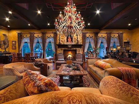 Phòng khách với thiết kế đèn chùm, đèn trần xa hoa cùng hệ thống lò sưởi, nệm gối cổ điển, điểm nhấn đặc biệt nhất là bức tranh của Michael Jackson treo ở giữa phòng