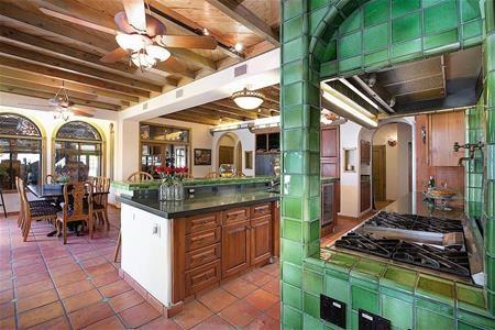 Phòng bếp với bờ tường ốp gạch hoa xanh, thể hiện phong cách kiến trúc Địa Trung Hải đậm đặc