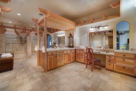 Một trong 12 phòng tắm của biệt thự, với một vòi hoa sen lớn, một bàn trang điểm và ba bồn rửa mặt