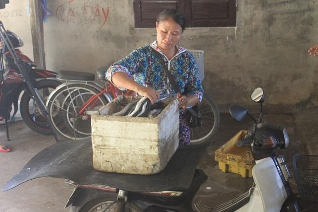 Bà Bình buồn bã khi phải chở nguyên thùng cá không bán được trong phiên chợ sáng