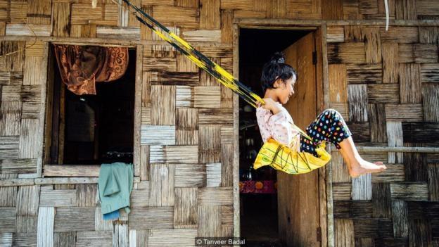 Một em nhỏ chơi trước hiên nhà, trên một chiếc xích đu tự chế.