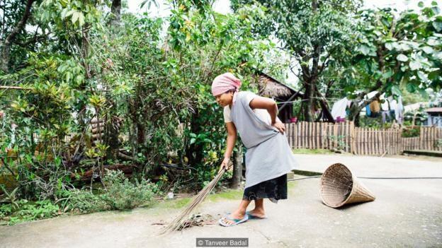 Người phụ nữ thu gom rác trên đường.