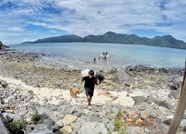 Vũ Hoài Nam – kiểm lâm tại hòn Tre Lớn – Côn Đảo nhận thức ăn do cano tiếp tế từ đảo Lớn ra