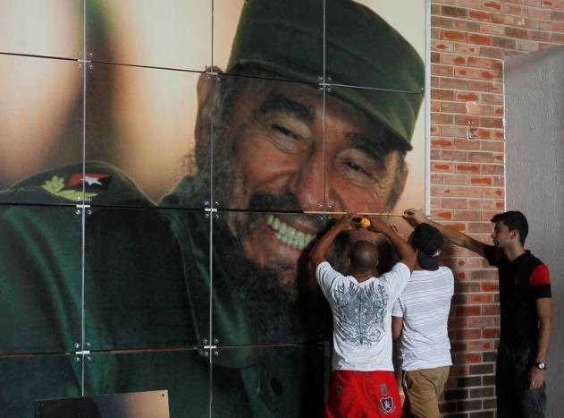 Công nhân treo chân dung Fidel Castro tại một trung tâm hội nghị ở Havana.