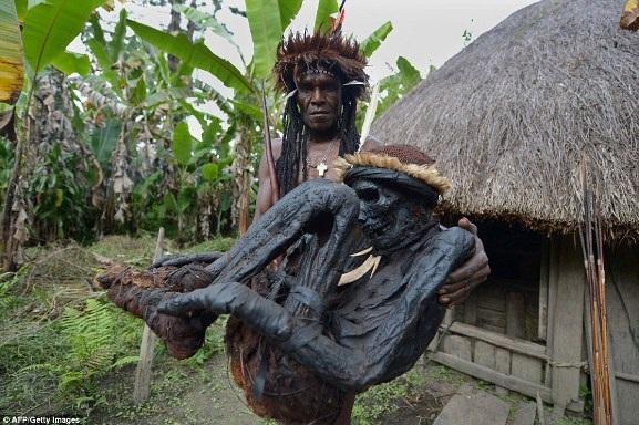 Trong ảnh là tộc trưởng Eli Mabel đang bê hài cốt của Agat Mamete Mabel ở làng Wogi, ở Wamena, Tây Papua, một hòn đảo thuộc trung tâm Papua New Guinea
